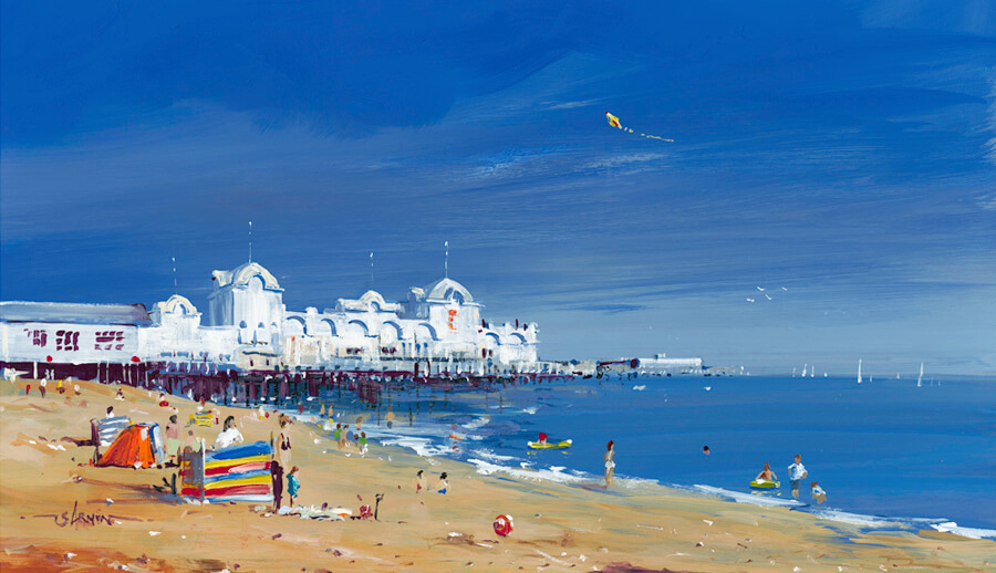 Acrylic painting of South Parade Pier, Southsea, Portsmouth by Steve Armon. Shows a typical summers day on Southsea beach, people on the beach and in the sea, a colourful windbreak is in the foreground and a kite flies in the blue sky.